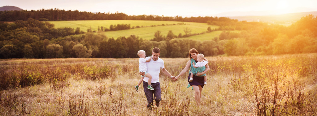 Young Family walking in a field while the sun sets.